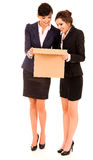 Two happy young business women with carton box, standing and smi Stock Photo