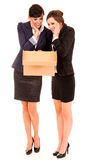 Two happy young business women with carton box, standing and smi Royalty Free Stock Photography