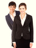 Two happy young business women standing and smiling Stock Photos