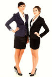 Two happy young business women standing and smiling Stock Images