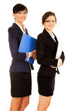Two happy young business women standing and smiling Royalty Free Stock Image