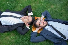 The two happy young businessmen in a suit lying on Stock Photos