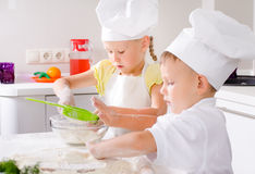 Two happy young children learning to bake Stock Photos