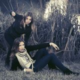 Two young fashion girls by lake in autumn park Royalty Free Stock Image