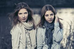 Two happy young fashion girls walking by the lake Stock Photo