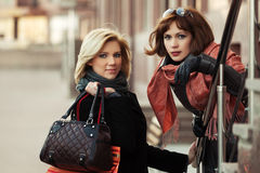 Two happy young fashion women on the city street Royalty Free Stock Image