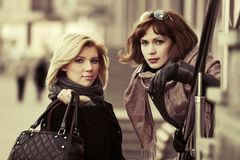 Two happy young fashion women on a city street Royalty Free Stock Photography