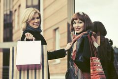 Two young fashion women with shopping bags next to mall door. Two happy young fashion women with shopping bags next to mall door Royalty Free Stock Photography