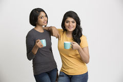 Two happy young female friends with coffee. Two happy young female friends posing with coffee cups on white background Stock Photography