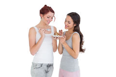 Two happy young female friends eating pastry together Stock Photos