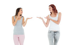 Two happy young female friends holding out their hands Stock Photo