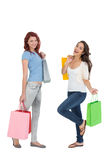 Two happy young female friends with shopping bags Royalty Free Stock Photo