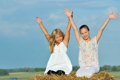 Two happy young girl friends enjoying the nature. In the hay Royalty Free Stock Photos
