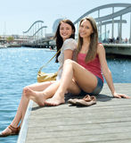 Two happy young girl sitting on the berth Stock Photo