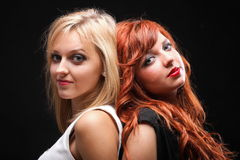 Two happy young girlfriends black background. Two happy young girlfriends blonde and red-hair black background Glamour stock photo