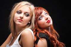 Two happy young girlfriends black background. Two happy young girlfriends blonde and red-hair black background Glamour stock photography