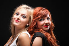 Two happy young girlfriends black background. Two happy young girlfriends blonde and red-hair black background royalty free stock photos