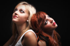 Two happy young girlfriends black background. Two happy young girlfriends blonde and red-hair black background Glamour stock photos