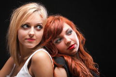 Two happy young girlfriends black background. Two happy young girlfriends blonde and red-hair black background Glamour royalty free stock photo