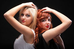 Two happy young girlfriends black background. Two happy young girlfriends blonde and red-hair black background Glamour royalty free stock image