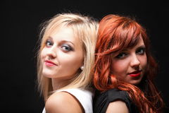 Two happy young girlfriends black background. Two happy young girlfriends blonde and red-hair black background Glamour stock image