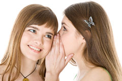 Two happy young girlfriends telling secret