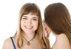 Two happy young girlfriends telling secret Royalty Free Stock Images