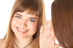 Two happy young girlfriends telling secrets Royalty Free Stock Image