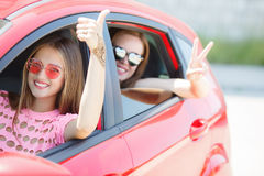 Two happy young girlfriends traveling in the car. Stock Image