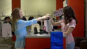 Two happy young girls are buying clothes at a cash desk in a department store. Slow Motion stock footage