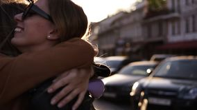 Two happy young girls hug each other. Females embracing, laughing and excited. Woman friendship, walk in the city. Outdoors. City view, sunlight on the stock video footage