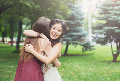 Two happy young girls hug each other in summer park Royalty Free Stock Photo