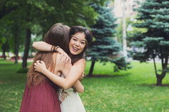 Two happy young girls hug each other in summer park Stock Images