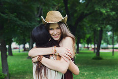 Two happy young girls hug each other in summer park Stock Photography