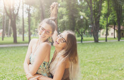 Two happy young girls hug each other in summer park Royalty Free Stock Photos