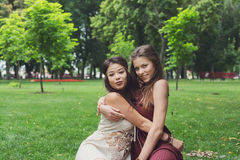 Two happy young girls hug each other in summer park Royalty Free Stock Images