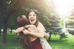 Two happy young girls hug each other in summer park Stock Photo