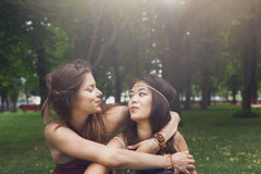 Two happy young girls hug each other in summer park Stock Image