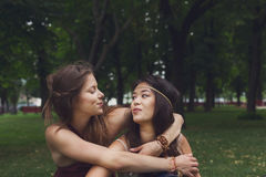 Two happy young girls hug each other in summer park Stock Photos