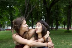 Two happy young girls hug each other in summer park. Two happy girls hug each other, friends embrace. Woman friendship, walk in the park outdoors Stock Photos