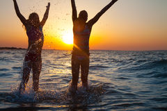 Two  happy young girls jumping at the beach Royalty Free Stock Image