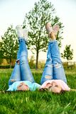 Two happy young girls lie on the grass Stock Photography