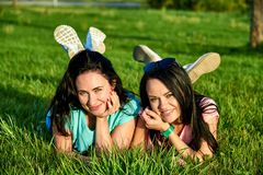Two happy young girls lie on the grass Royalty Free Stock Image