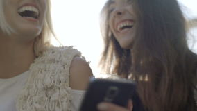 Two happy young girls looking at smart phone and having fun, outdoor. Beautiful cheerful women using phone and drinking orange cocktails Friendship and stock footage