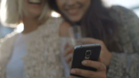 Two happy young girls looking at smart phone and having fun, outdoor. Beautiful cheerful women using phone and drinking orange cocktails Friendship and stock video
