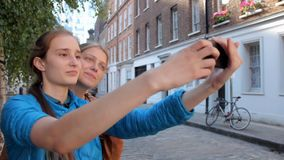 Two happy young girls taking selfie, fooling around, discussing and talking. Walking the streets of London, laughing and stock video