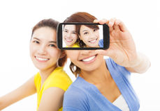 Two happy young girls taking a selfie over white Stock Photo