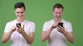 Two happy young handsome men using phones together. Studio shot of two young handsome men together against chroma key with green background stock video footage