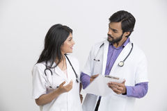 Two happy young Indian attractive doctors discussion with document. Stock Photos