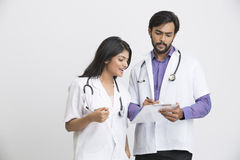 Two happy young Indian attractive doctors talking with document. Stock Photography